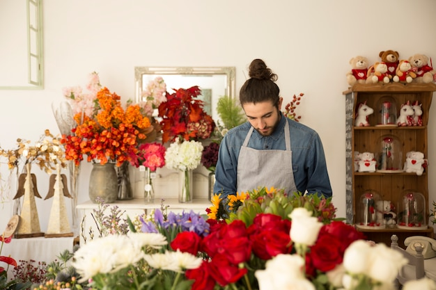カラフルなフラワーショップで働く男性の花屋のクローズアップ 無料写真