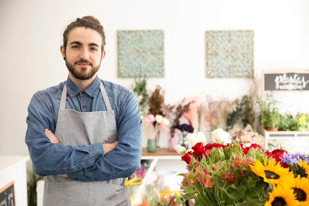 彼のフラワーショップで自信を持って男性の花屋の肖像画 無料写真