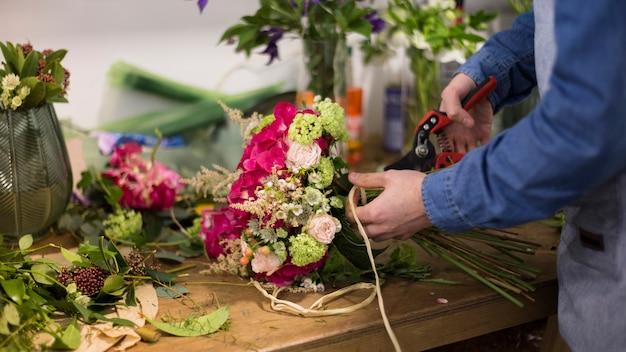 フラワーショップで花の花束を作成する男性の花屋のクローズアップ 無料写真