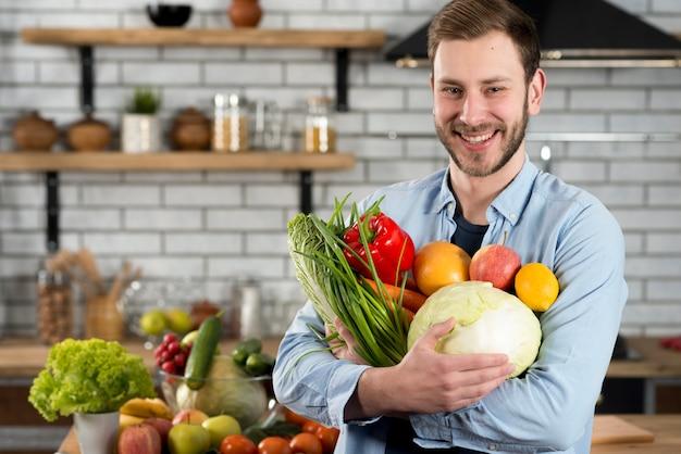 生野菜と台所に立っている幸せな男 無料写真