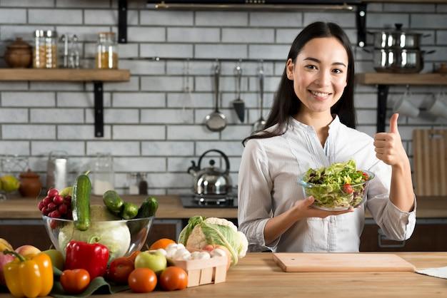 野菜サラダを保持しているサインを親指を示すキッチンカウンター近くに立っている若い女性 無料写真