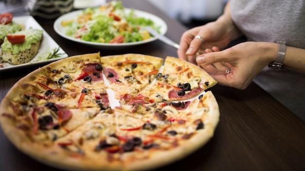 プレートからペパロニピザのスライスを取って女性の手のクローズアップ 無料写真