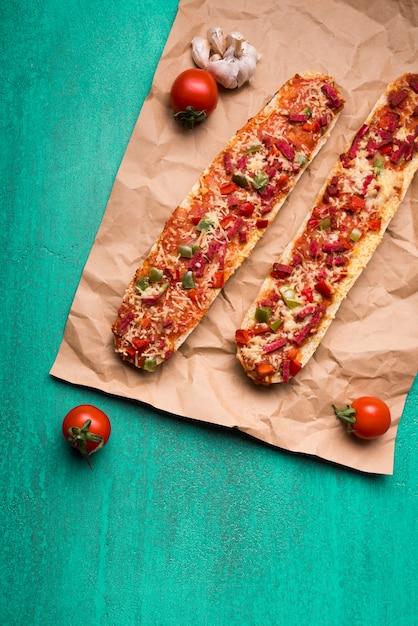 チェリートマトとターコイズブルーの背景の上にニンニクと茶色の紙の上の新鮮なおいしいバゲットピザ 無料写真