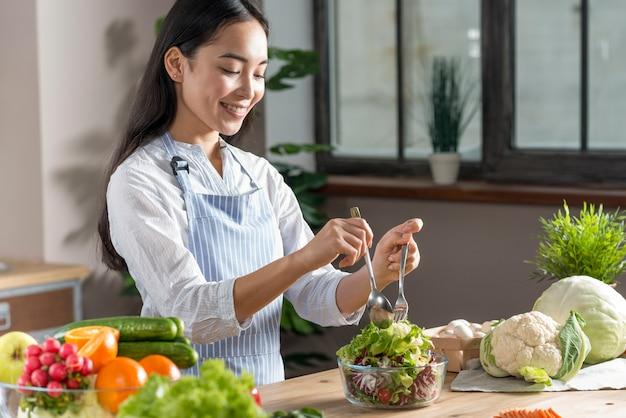 幸せな女の台所でヘルシーサラダを準備します。 無料写真