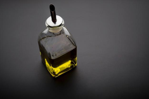 暗い背景にオリーブオイルの瓶 無料写真