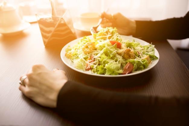 レストランでエビとシーザーサラダを食べる人 無料写真