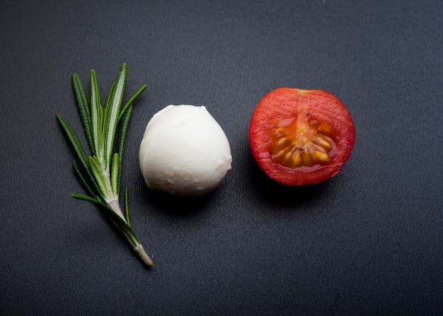 グリーンローズマリー。黒い表面上の半分の陽気なトマトとモッツァレラチーズ 無料写真
