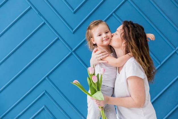 母は青い背景上のチューリップの花を保持している彼女のかわいい娘にキス 無料写真