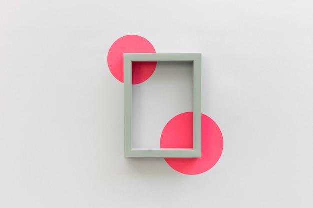 白い背景の上の円形用紙とフォトフレームの枠線の高角度のビュー 無料写真