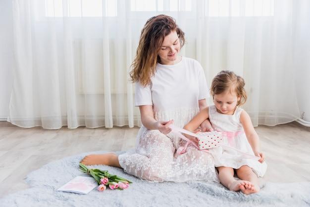 Мать и дочь, сидя на ковре с подарочной коробке; цветы и поздравительная открытка Бесплатные Фотографии