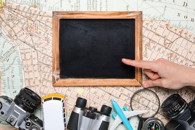 旅行の要素に囲まれた黒板に手 無料写真