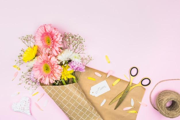 ママの単語とはさみのタグの近くのラップで新鮮な花の花束 無料写真