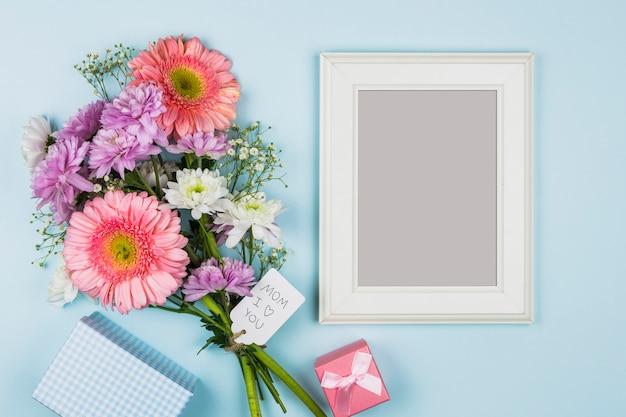 パケット、プレゼント、ノートブックの近くのタグのタイトルと生花の近くのフォトフレーム 無料写真