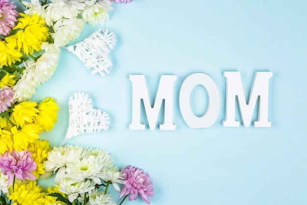 心と新鮮な花の束の近くのお母さんの言葉 無料写真