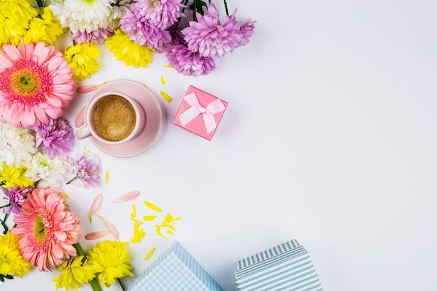 一杯の飲み物、プレゼントボックス、花びらの近くの新鮮な花 無料写真
