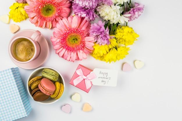 プレゼント、一杯の飲み物、ボウルにマカロンのタグと近くの新鮮な花 無料写真