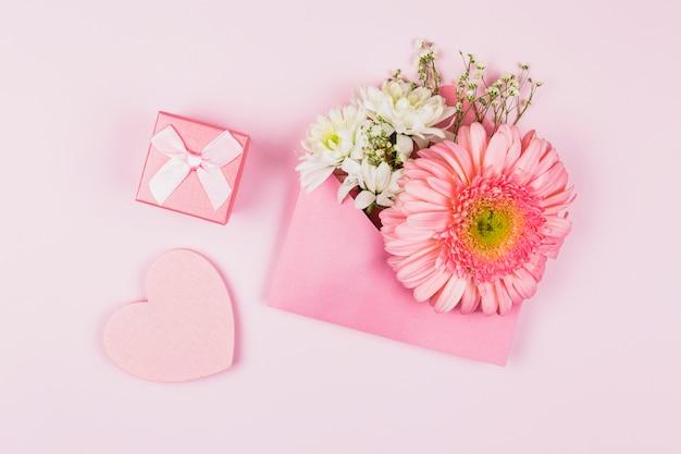 Композиция из живых цветов в конверте возле настоящего и декоративного сердца Бесплатные Фотографии