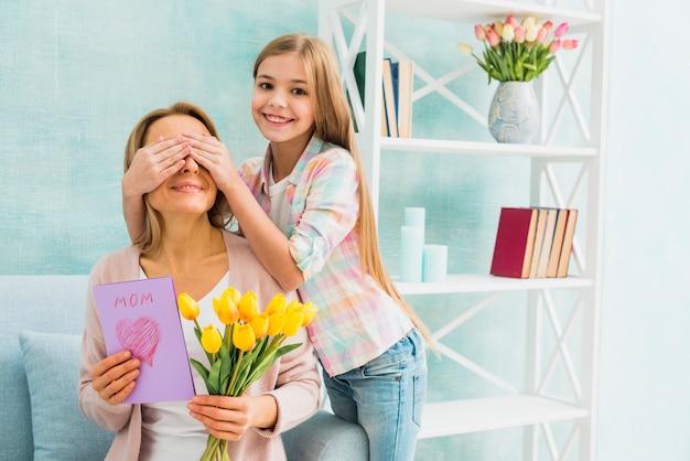 Дочь улыбается и закрывает глаза маме с подарками Бесплатные Фотографии