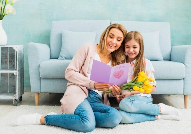 Мать с дочерью читает открытку ко дню матери Бесплатные Фотографии