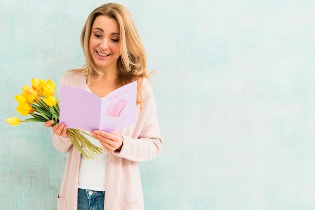 Счастливая женщина читает открытку на день матери Бесплатные Фотографии