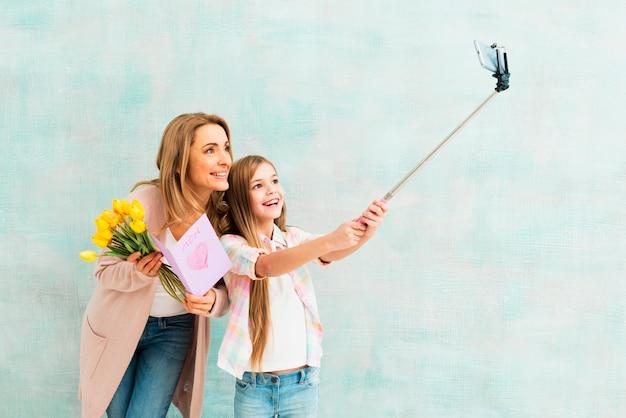 Дочь и мать, улыбаясь и принимая селфи Бесплатные Фотографии