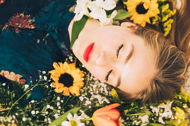 魅力的な魅力的な女性は花の間に横たわる 無料写真