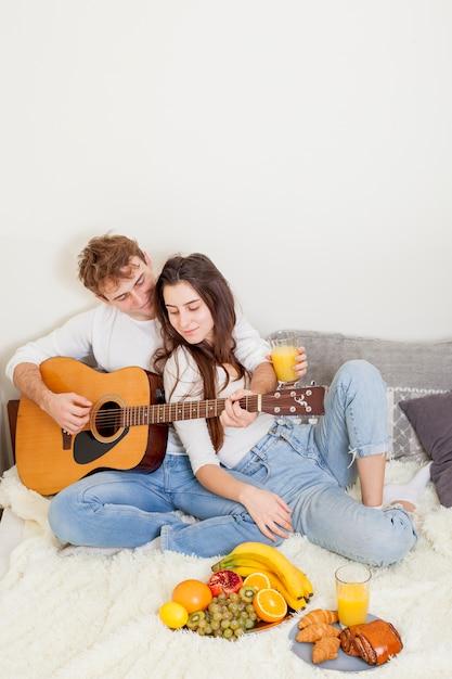 ベッドで朝食を持っている若いカップル 無料写真