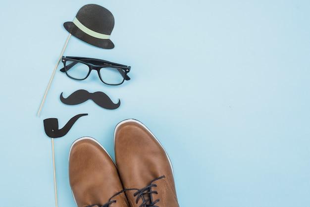 メガネと紙の口ひげを持つ男の靴 無料写真