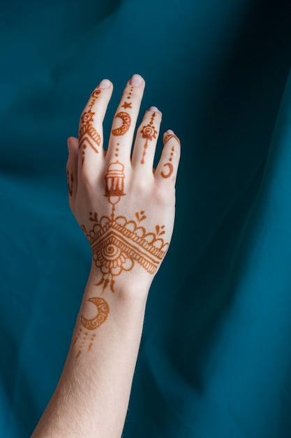 Женская рука с менди возле синей ткани Бесплатные Фотографии