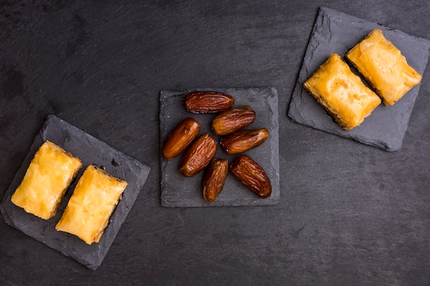 黒いテーブルの上の東部のお菓子とドライデートフルーツ 無料写真