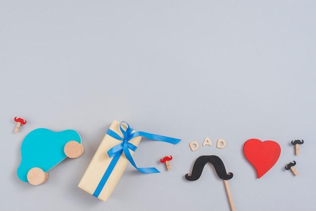 ギフト用の箱、おもちゃの車、紙の口ひげとお父さんの碑文 無料写真