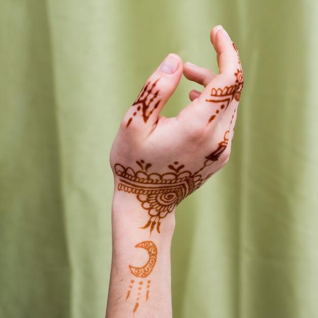 Женская рука с менди рисует возле текстиля Бесплатные Фотографии