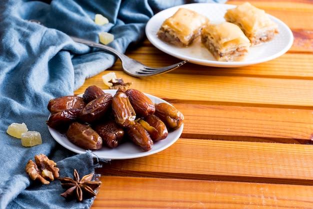 木製のテーブルの東のお菓子とドライデートフルーツ 無料写真