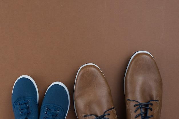 Мужская и детская обувь на коричневом столе Бесплатные Фотографии