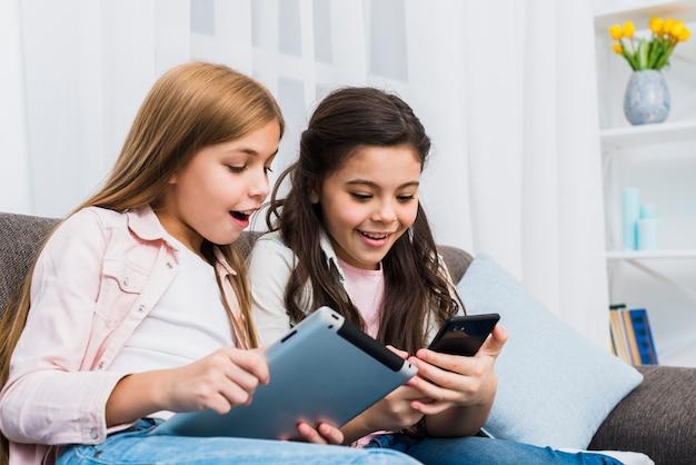 デジタルタブレットと携帯電話を使用してソファーに座っていた幸せな女友達 無料写真