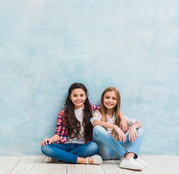塗られた水色の壁に対して一緒に座っている二人の笑顔の女の子の肖像画 無料写真