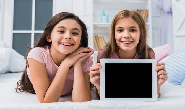 空白の画面デジタルタブレットを示すベッドの上に彼女の友人と敷設笑顔の女の子 無料写真