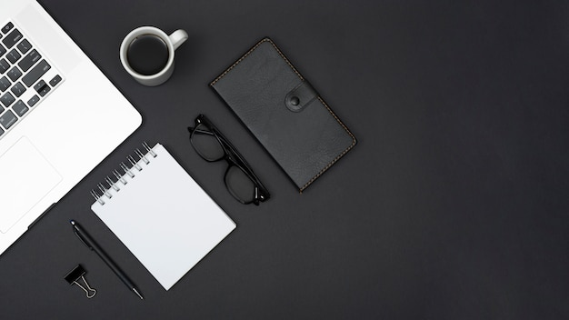 ノートパソコンの平面図。お茶;ペン;スパイラルメモ帳。メガネ。黒い背景に日記とペーパークリップ 無料写真