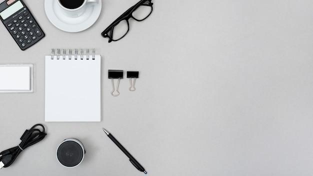 電卓に囲まれた空白のスパイラルメモ帳。ティーカップペーパークリップ;スピーカー;ペン;灰色の背景上のケーブルと眼鏡 無料写真