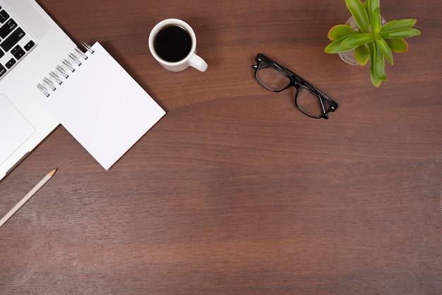Завод; очки для глаз; чай; пустой спиральный блокнот и карандаш с ноутбуком на деревянный стол Бесплатные Фотографии