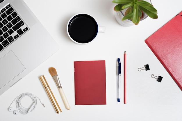 Вид сверху ноутбука; чашка кофе; наушники; и ручка; косметическая кисточка; тушь для ресниц; растение в горшке на белом фоне Бесплатные Фотографии