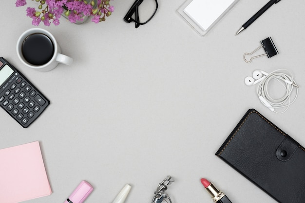 化粧品のハイアングル。事務用文房具;コーヒーカップ;灰色の背景に配置された眼鏡 無料写真