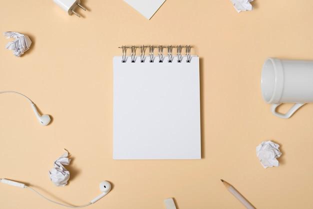 Пустой белый блокнот в окружении пустой чашки; мятой бумаги; карандаш; наушники на бежевом фоне Бесплатные Фотографии