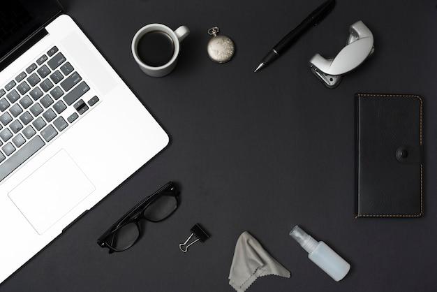 黒いテーブルの上のノートパソコンとコーヒーカップのトップビューオフィスもの 無料写真