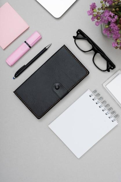 灰色の背景上の文房具と眼鏡の高角度のビュー 無料写真