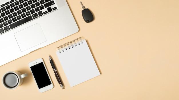 コーヒーカップ付きラップトップ。携帯電話;そして空白の日記。ベージュ色の背景に対してペン 無料写真