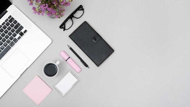 コーヒーカップと灰色の背景に文房具付きのノートパソコンのトップビュー 無料写真