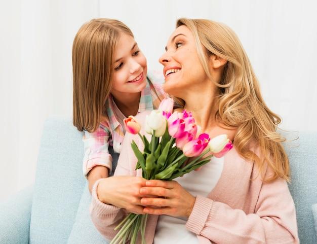 娘を見てチューリップと満足ママ 無料写真