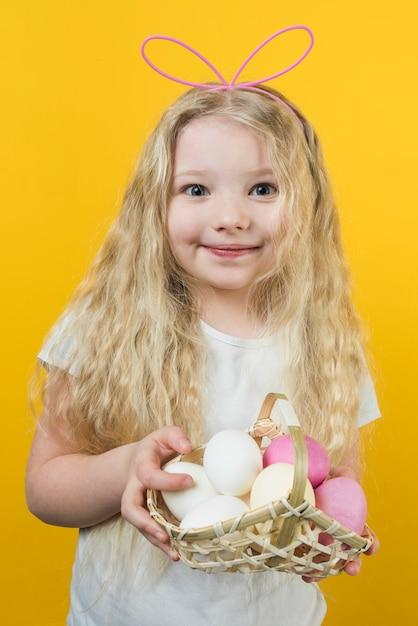 Девушка в ушах зайчика держит корзину с пасхальными яйцами Бесплатные Фотографии
