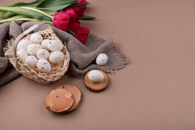 Белые куриные яйца в корзине с красными тюльпанами Бесплатные Фотографии